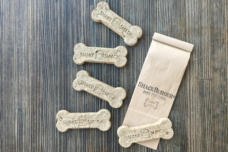 "Image of five spread out bones showing the Shake Shack Burger logo, with bag for bones to go into saying ""Shack Burger Dog Biscuits"""