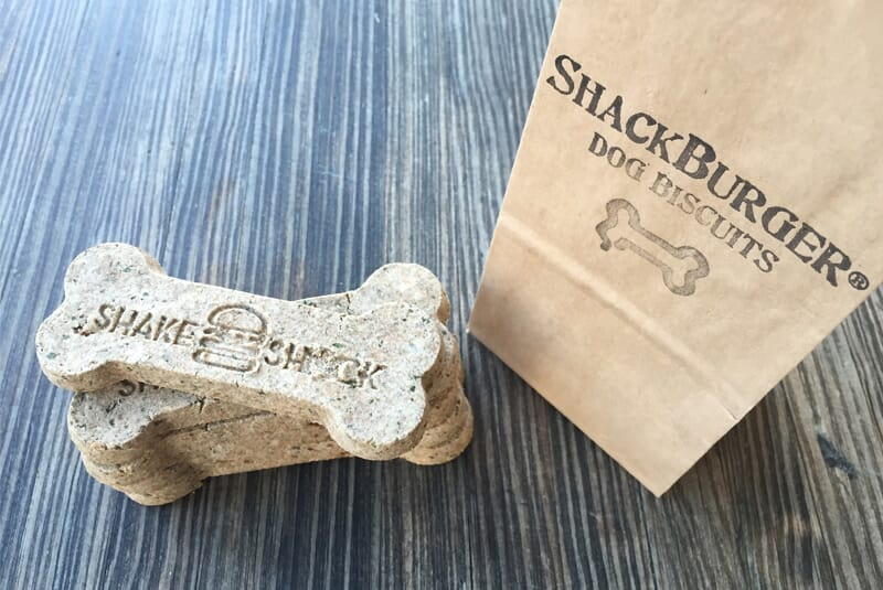 "Image of five stacked bones showing the Shake Shack logo, with bag next to them saying ""Shack Burger Dog Biscuits"""