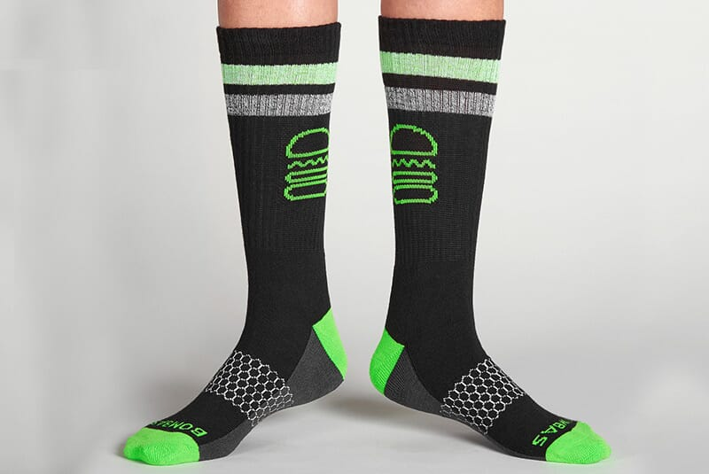 Image of the socks on male feet standing with toes pointed outward.