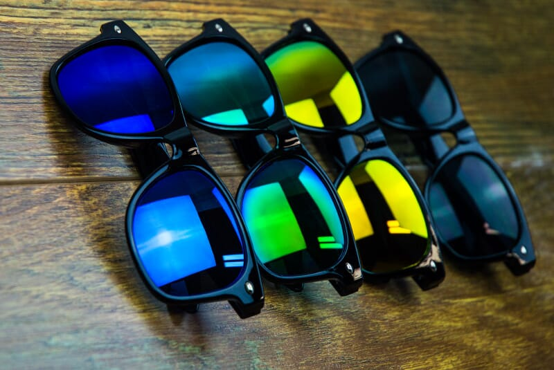 Black, warm, cool and indigo colored Shake Shack Shades in a line.