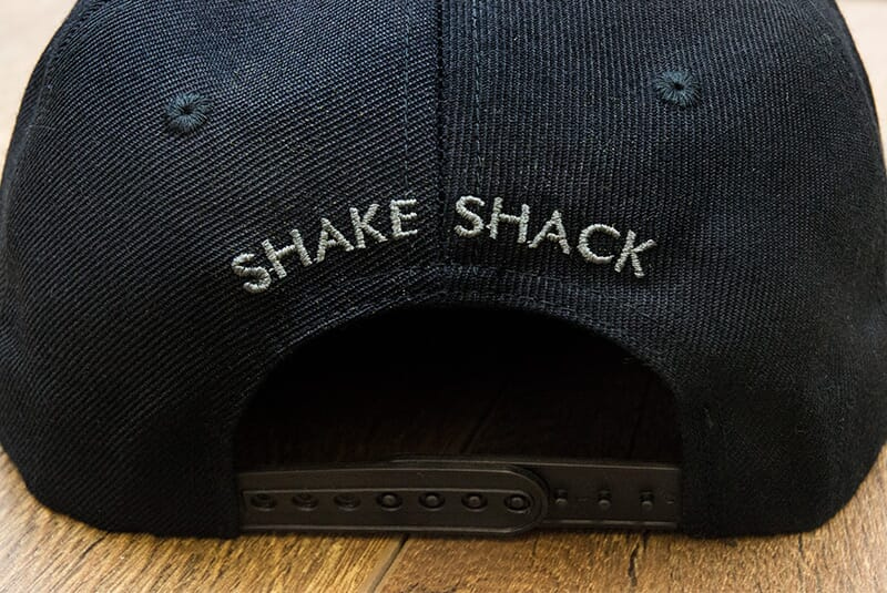 "Image showing back of hat with grey logo ""Shake Shack"" arching."