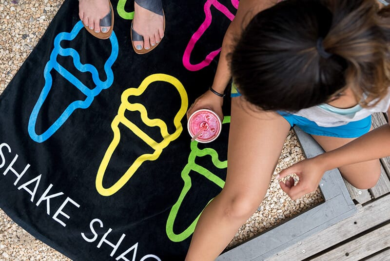 "Image of Shack Towel laid out on the ground with people sitting on it. Image shows how towel has multiple colors of ice cream cone, including green, yellow, blue and pink. The words ""Shake Shack"" are at the bottom of the towel."