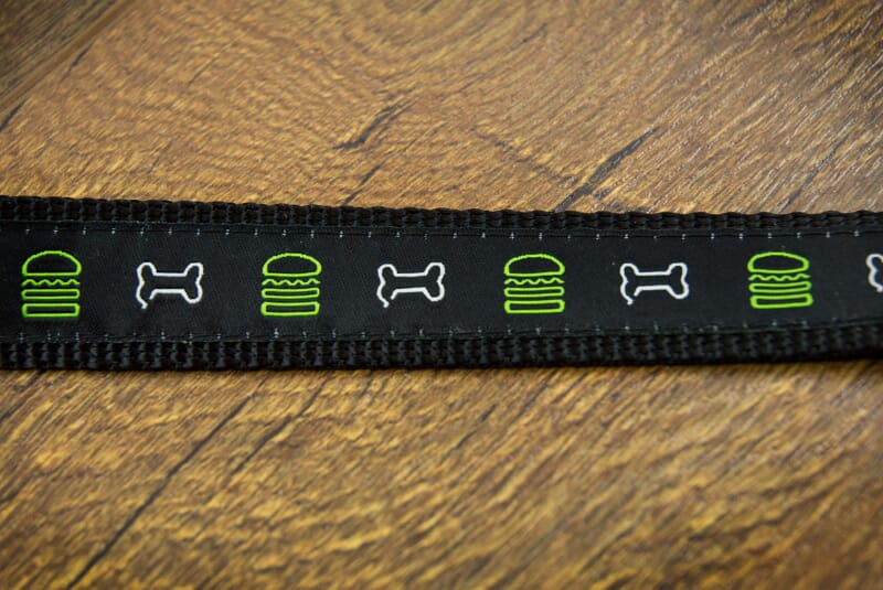 Image of leash close up showing a line of a green burger and a white bone, green burger white bone continuously.