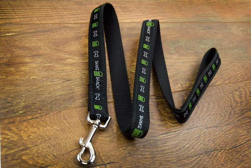 Image of Shake Shack Dog Leash from different angle showing a continuous line of a green burger, a white dog bone, and the Shake shack logo from one end of the leash to the end.