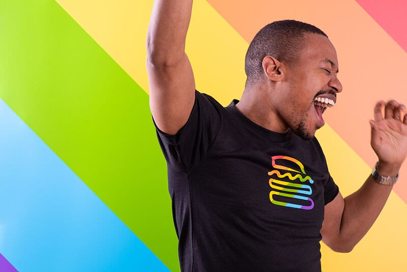 Image of man smiling with pride tee.
