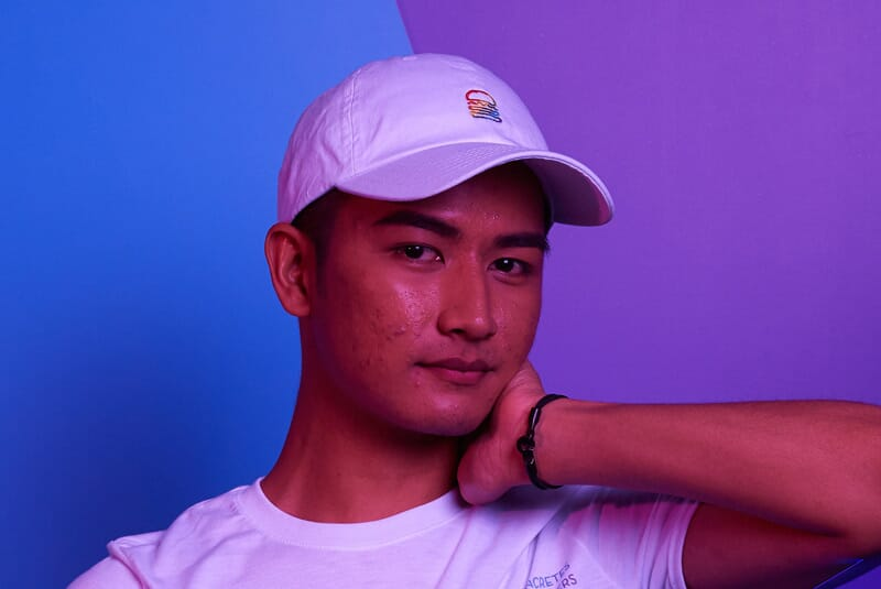 Close up image of one person wearing Rainbow Burger Cap