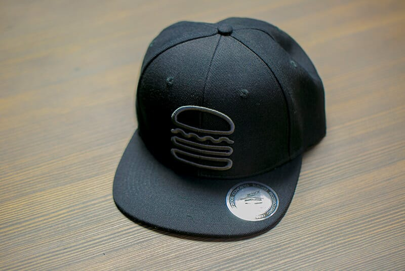 Far side image of Black Snapback hat with grey hamburger logo.